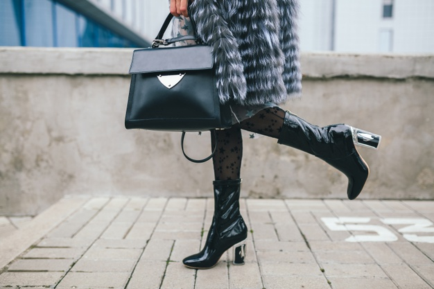 close-up-accessories-details-stylish-woman-walking-city-warm-fur-coat-winter-season-cold-weather-holding-leather-handbag-legs-boots-footwear-street-fashion-trend_285396-4720