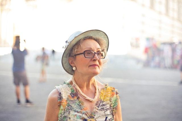 Staršia žena vo farebných šatách a klobúku s výrazným náhrdelníkom a náušnicami.jpg
