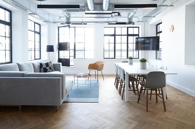 Moderne zariadený byt s veľkou pohovkou, jedálenským stolom a veľkými oknami