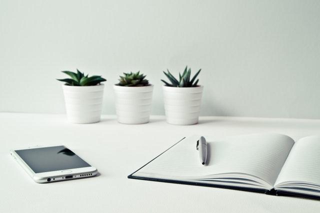 Biely stôl, notes, okuliare a tri biele kvetináče so zelenými sukulentami