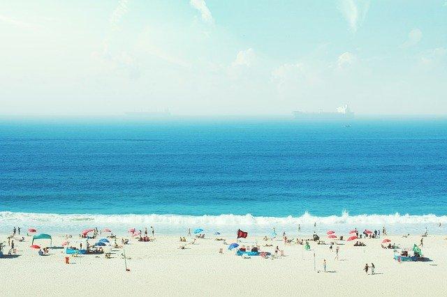 Pláž s bielym pieskom. Množstvo turistov a slnečníky.jpg