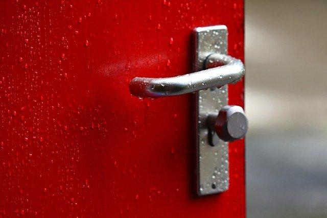 Červené pootvorené dvere so striebornou kľučkou.jpg