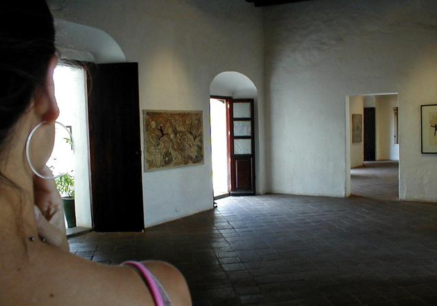 Žena stojí v dome s viacerými otvorenými a zatvorenými dverami.jpg