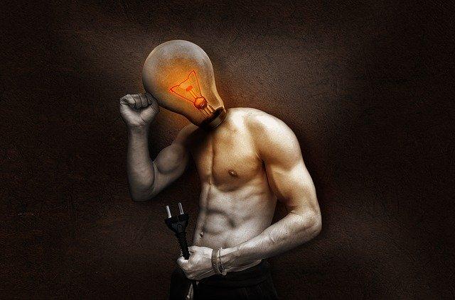 Svalnatý muž, ktorý má na miesto hlavy žiarovku a drží kábel v ruke.jpg