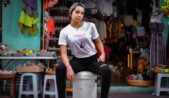 Žena v bielom tričku, čiernych legínach a šatkou na hlave sedí pred obchodom.jpg